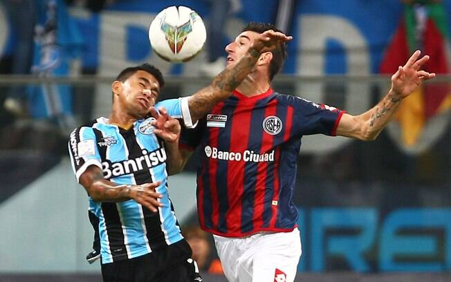 Dudu, autor do gol do Grêmio diante do San Lorenzo, disputa a bola com Catalan